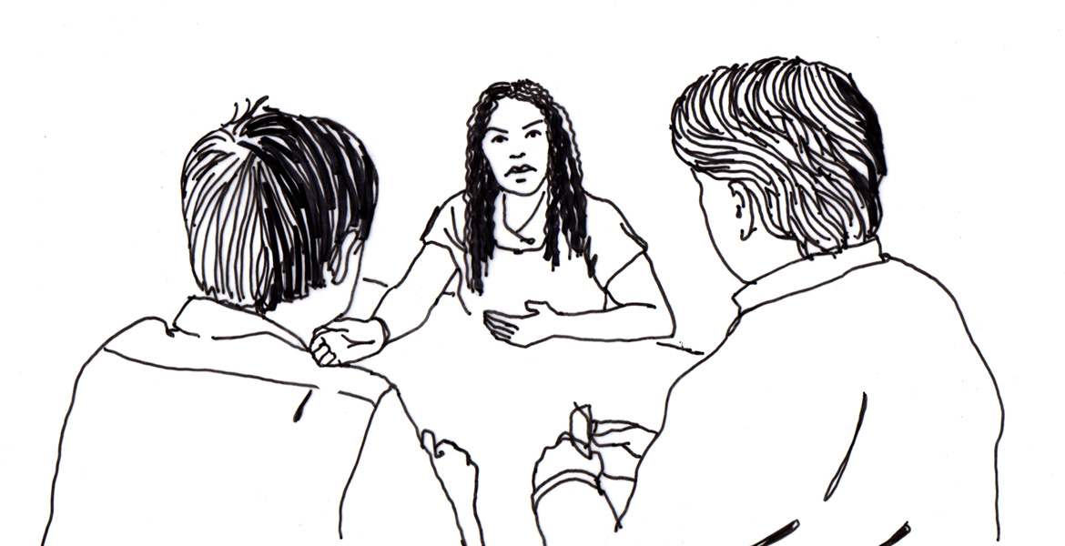 3 people talking at a table